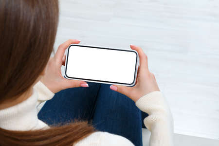Rear view of girl using phone with white blank screen mockup. Lifestyle concept with digital technology.