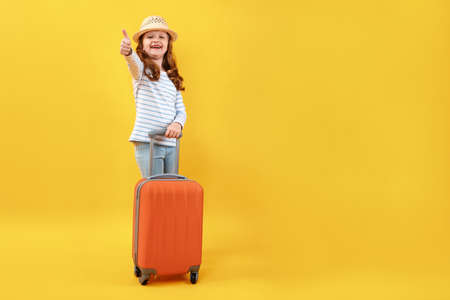Cheerful full-length preteen girl with an orange suitcase on a yellow background. The child smiles and shows a thumb up.