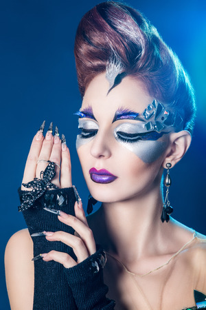 Beautiful woman with stylish hair style, art make up with silver shadows, purple lips and shards of broken mirror. Very long nails new shape manicure nail extension. Full fashion look. Beauty portrait photo