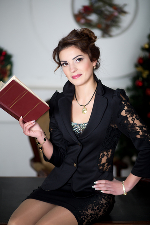 table skirt: Beautiful smiling woman with natural make up, stylish hair dress, black business suit costume - skirt lace jacket. Office interior, white wall, seating on wooden table, reading book or notebook, diary