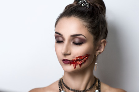 demoniacal: Female vampire with blood stains stage blood. Pretty woman with perfect face, smoky eyes, bright red lips sexy mouth, professional art make up. Evil crime murderer, offence furious lady, be a victim Stock Photo