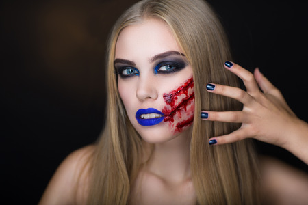 portrait young girl studio: Beautiful girl with creative make-up for the Halloween party. Bright colors faceart, blue lips, long hair dress design. A long wound cheek, trickle of blood flows, realistic effects, crazy art idea
