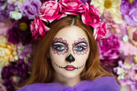 face: Day of the Dead, Skull Mask. Art woman beautiful face painted as a traditional day of the dead, pink flowers on head. Free place on photo for congratulations. Good for Halloween card, present, banner
