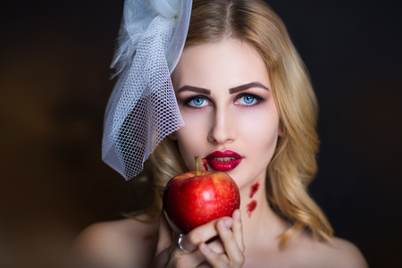 poisoned: Beautiful girl with creative make-up for the Halloween party. Bright colors eyes, red lips, stylish hair dress design. Conceptual art Snow White, character eating big poisoned apple, vampire bite neck Stock Photo