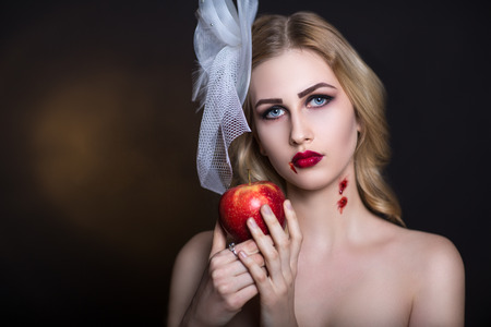 snow white: Beautiful girl with creative make-up for the Halloween party. Bright colors eyes, red lips, stylish hair dress design. Conceptual art Snow White, character eating big poisoned apple, vampire bite neck Stock Photo