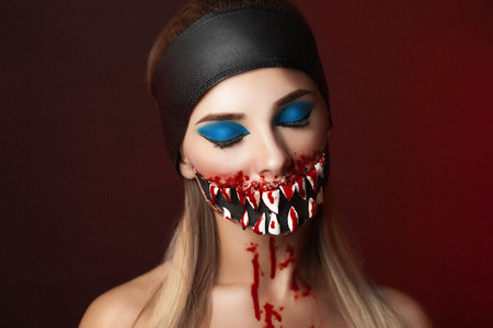 Character with big teeth and black mouth. Professional make up for horror film faceart, bodyart, aqua grim, cosmetics. Realistic photo. Can be used for Halloween party, studio horror, milena, milina