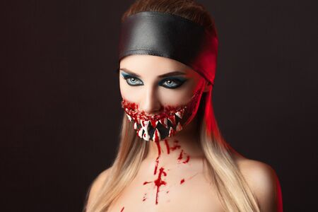 demonic: Character with big teeth and black mouth. Professional make up for horror film faceart, bodyart, aqua grim, cosmetics. Realistic photo. Can be used for Halloween party, studio horror, milena, milina