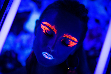 black blue: Woman face with fluorescent make up art. Blue background. Studio shot. Orange, pink, blue neon paints. Creative idea is good for clubs, disco, go-go, show concerts, parties. Sexy girl alien cosmo new Stock Photo