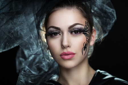 fantasy makeup: Pretty woman with black picture on skin part of face. Perfect idea for advertisement, banner, Halloween party card. sexy lips, black widow in a transparent veil, a dead bride preparing for the wedding