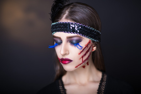 sores: Pretty woman wound knife splinter in the skin, bloody part of face. Perfect idea for new advertisement, banner, Halloween party card. Cosplay idea beauty monster red blood lips. Young beautiful face