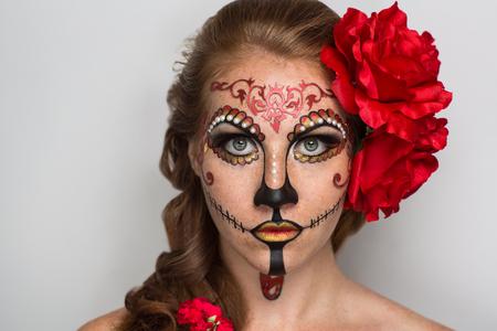 dia de muertos: D�a de los Muertos, la m�scara de cr�neo. Hermosa cara de mujer pintado como un d�a tradicional de las, flores rojas muertas en la cabeza. Lugar gratuito en la foto para las felicitaciones. Bueno para la tarjeta de Halloween, presente, bandera Foto de archivo