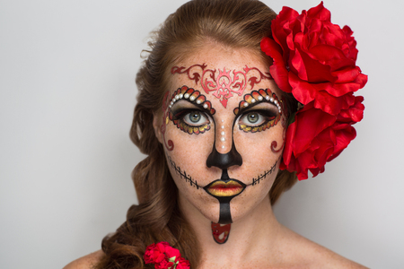 redhead girl: Day of the Dead, Skull Mask. Art woman beautiful face painted as a traditional day of the dead, red flowers on head. Free place on photo for congratulations. Good for Halloween card, present, banner