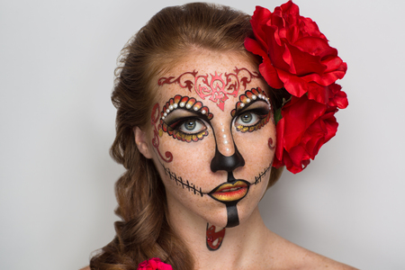 Day of the Dead, Skull Mask. Art woman beautiful face painted as a traditional day of the dead, red flowers on head. Free place on photo for congratulations. Good for Halloween card, present, banner