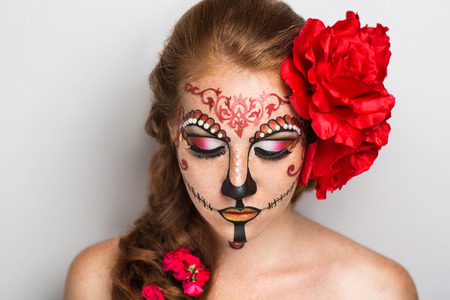 wicked woman: Day of the Dead, Skull Mask. Art woman beautiful face painted as a traditional day of the dead, red flowers on head. Free place on photo for congratulations. Good for Halloween card, present, banner