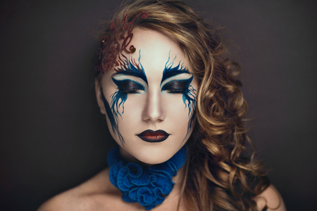 Portrait of a beautiful girl with an original makeup painted on young pretty face, red  blue waves, golden curly hair, expressive lips and flawless model appearance. Creative body art  painting idea Stock Photo