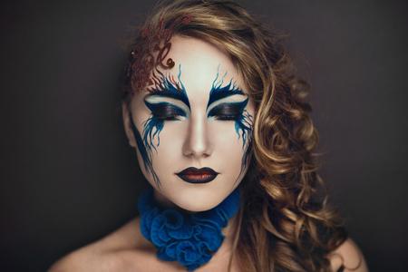 maquillaje de fantasia: Retrato de una hermosa chica con un maquillaje original pintada en el rostro joven y bonita, olas azules rojos, pelo rizado de oro, labios expresivos y apariencia modelo impecable. Cuerpo creativo idea pintura del arte Foto de archivo