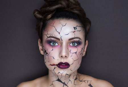 damaged: Beautiful girl with creative make-up for the Halloween party. Bright colors faceart, red lips, stylish hair dress design. Conceptual art broken porcelain doll with big cracks on the cheeks, forehead