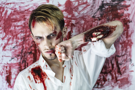 horror: Handsome man with an open fracture of the hand, white bones of the forearm dropped out, a painful injury, scars on face. Standing near bloody wall background, scene from horror film or Halloween party Stock Photo