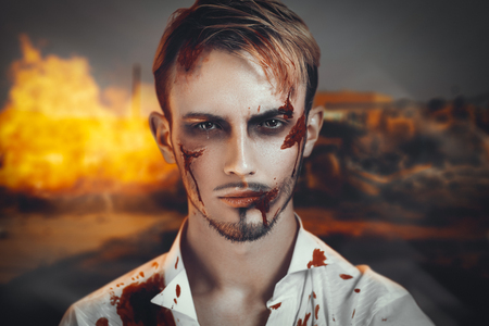 suffered: Portrait of a man who suffered during the war, was the victim of terrorist attack. Beautiful face disfigured with scars, wounds, bloody streaks. hero of the country which destroyed the enemy invaders Stock Photo