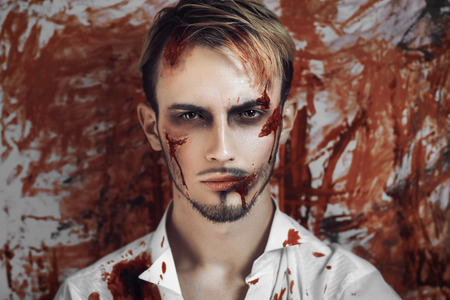 Man with bleeding face. Professional make up for horror film makeup faceart bodyart aqua grim, cosmetics. Realistic photo. Can be used for Halloween party, vampire, saloon, studio of horror, crazy