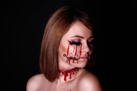 Pretty woman wound knife splinter in the skin, bloody part of face. Perfect idea for advertisement, banner, Halloween party card. Cosplay idea beauty monster red sexy shoulders blood lips. Young face Stock Photo