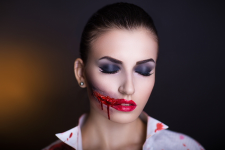 splinter: Pretty woman wound knife splinter in the skin, bloody part of face. Perfect idea for advertisement, banner, Halloween party card. Cosplay idea beauty monster red sexy shoulders blood lips. Young face Stock Photo