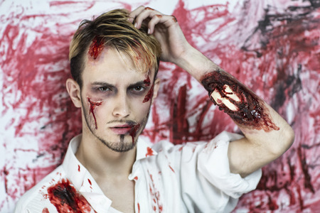 scars: Handsome man with an open fracture of the hand, white bones of the forearm dropped out, a painful injury, scars on face. Standing near bloody wall background, scene from horror film or Halloween party Stock Photo