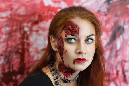 cut glass: Pretty woman wound glass splinters in the skin, standing near bloody wall. Perfect idea for advertisement, banner, Halloween party card. Cosplay idea beauty monster, red sexy blood lips. Young face Stock Photo
