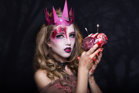 vile: Vampire Queen holds great human heart pig or bull heart in her hands. Vile worms and needles sticking out of the heart. Pink crown decorate her head with golden curly hair. Bullet wounds on forehead Stock Photo