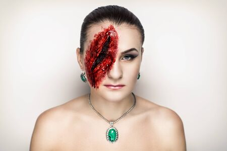 cut glass: Pretty woman wound knife splinter in the skin, bloody part of face. Perfect idea for advertisement, banner, Halloween party card. Cosplay idea beauty monster red sexy shoulders blood lips. Young face Stock Photo