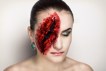 sores: Pretty woman wound knife splinter in the skin, bloody part of face. Perfect idea for advertisement, banner, Halloween party card. Cosplay idea beauty monster red sexy shoulders blood lips. Young face Stock Photo