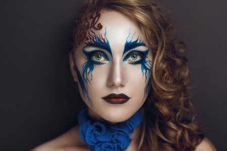 sea nymph: Portrait of a beautiful girl with an original makeup painted on young pretty face, red  blue waves, golden curly hair, expressive lips and flawless model appearance. Creative body art  painting idea Stock Photo
