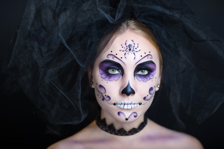 Day of the Dead, Skull Mask. Art woman beautiful face painted as a traditional day of the dead, spider net on head. Free place on photo for congratulations. Good for Halloween card present big banner Stock Photo