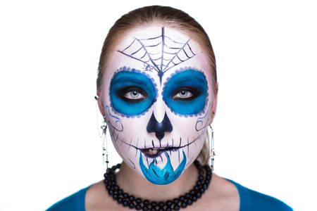 scared girl: Day of the Dead, Skull Mask. Art woman beautiful face painted as a traditional day of the dead, blue flowers on head. Free place on photo for congratulations. Good for Halloween card, present, banner