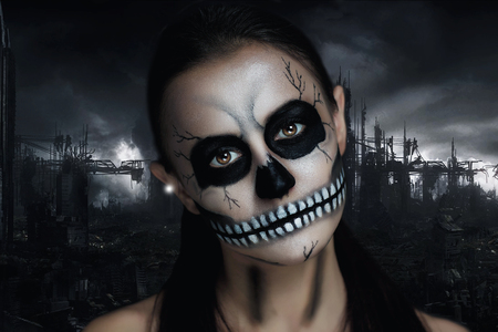 Dark girl with a terrible make-up for the Halloween party. Terrible skeleton of a revived corpse. The creative idea for the club, poster ads. Black background of the ruined city grey sky. Terrifying
