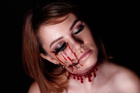 cut and blood: Pretty woman wound knife splinter in the skin, bloody part of face. Perfect idea for advertisement, banner, Halloween party card. Cosplay idea beauty monster red sexy shoulders blood lips. Young face Stock Photo