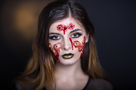 cheeks: Horror make-up. Beautiful girl with creative grim for the Halloween party or film. Bright colors faceart, face design, golden black lips. Conceptual art broken eyes, sharp spikes on cheeks, forehead