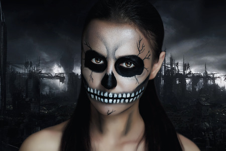 terrifying: Dark girl with a terrible make-up for the Halloween party. Terrible skeleton of a revived corpse. The creative idea for the club, poster ads. Black background of the ruined city grey sky. Terrifying