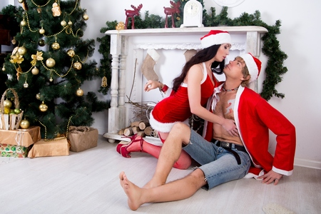 Young beautiful sexy couple man and woman husband and wife Santa Claus Snow Maiden love role-play passion seduction dominance relationships. Perfect Christmas look stylish outfit drawing. Stock Photo