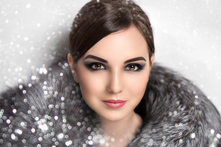 Portret van mooie jonge meisje, dame, vrouw, model, actrice, ster, beroemdheid. Winter, Nieuwjaar, Kerstmis, luxe, rijkdom. Elegante look, spectaculaire make-up, rokerige ogen, ideaal wenkbrauwen, chic kapsel Stockfoto