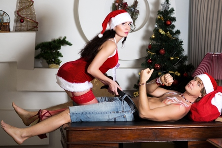 bondage girl: Young beautiful sexy couple man and woman husband and wife Santa Claus and Snow-maiden passion seduction dominance handcuffed relationship  role-playing game. Perfect Christmas stylish look.