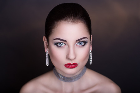 chic woman: Young beautiful woman lady model woman actress. Luxury bright stylish look. Chic impressive appearance. Perfect face smoky eyes makeup brown eyebrows arrows, sexy red lipstick lips. Necklace jewelry
