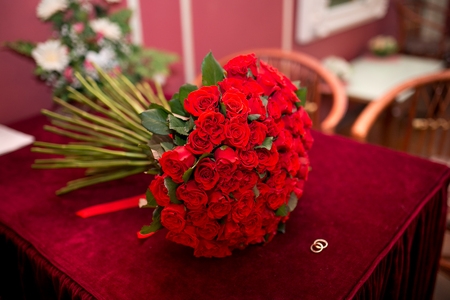 the next life: Big beautiful fragrant bouquet of red roses lying on a wooden table next to two small gold rings. Preparations for the wedding, luxury accessories and gifts for newlyweds, luxurious life rich people Stock Photo
