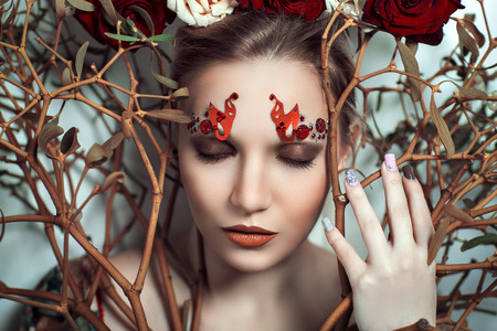 Beautiful young girl, lady, actress, model, character, tree, rose, fairy tale. Bold creative look, fashion style. Ideal expressive makeup, bright red lips, decor, accessory, headdress, branch, flowers