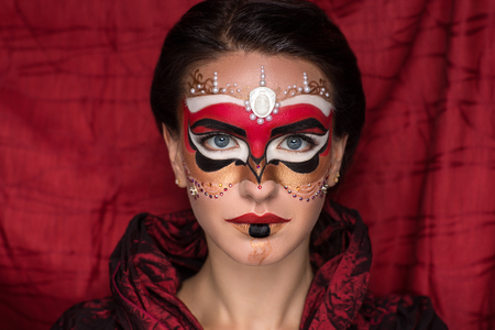intrigue: Portrait of beautiful young girl lady woman queen. Creative perfect makeup mask pattern bright colors. Chic hairstyle decorative ornaments. Carnival ball Venice luxury wealth travel around the world