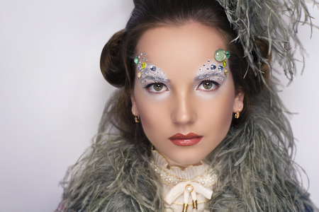 Portrait beautiful young elegant woman. Styling the image of medieval queen. High top hairstyle with hair raised, creative makeup silver white pearls, luxury ostrich feathers boa. vintage pathos grace