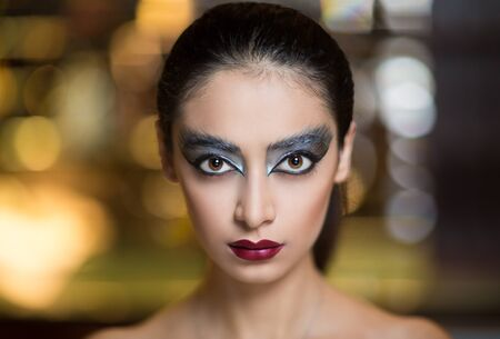 free place: Close-up portrait of beautiful woman with serious face, silver black art make up. Big shiny eye shadows, professional cosmetics new beauty trend. Free place of background blurred lights of city life. Stock Photo