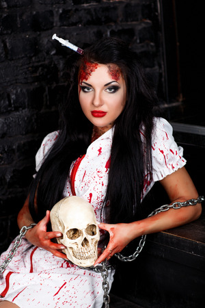 role play: Black haired beautiful   nurse from the hospital. Bloody Syringe sticking in the head and the brain follows. mad house role play game, Stock Photo
