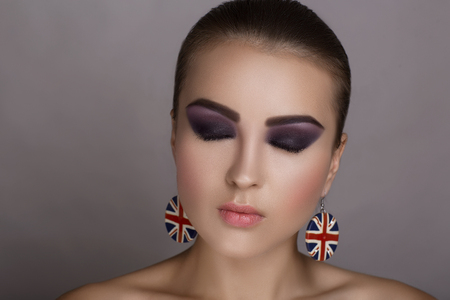 flawless: Portrait of beautiful young girl woman lady model. Flawless makeup, perfect shape of the eyebrows, bright smoky eyes pink lipstick, earrings. Image can be used for advertising of new cosmetic products