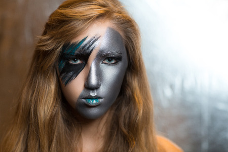 hitman: Woman with silver art make up part of face, blue lips. Portrait of beautiful young girl woman lady hitman killer techno future progress. Ideal creative expressive makeup. Stylish, bright, showy look.